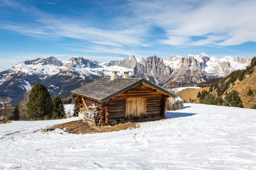 Alpine cottage nearby skiing slopes in Buffaure ski area, Val di Fassa valley, Dolomites mountains, Italy