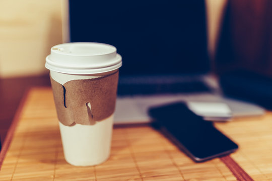 White paper Cup with burning coffee on the background of laptop and smartphone to Work on the go. Toned photo.
