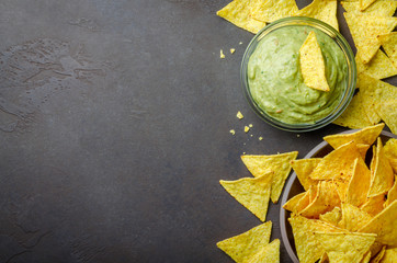Traditional mexican homemade guacamole sauce in a glass bowl and a bowl with tortilla chips on a dark black stone background. Party food concept.  Top view, copy space, horizontal