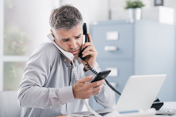 Stressed businessman having multiple calls