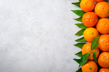 Fresh clementines on a light stone background. Top view, copy sp