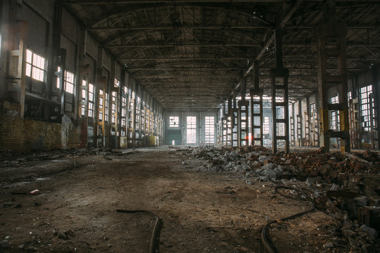 Dark creepy ruins of demolished abandoned large industrial warehouse or hangar of Soviet factory
