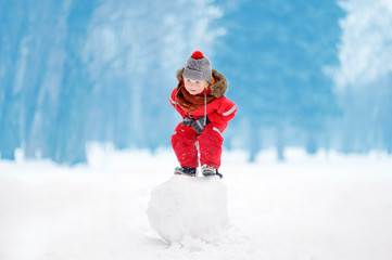 Little boy in red winter clothes having fun with snowball