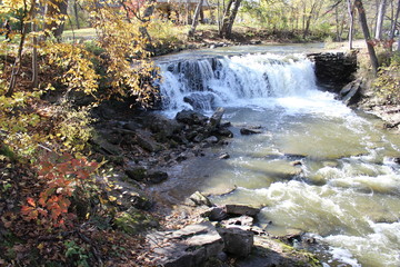 Shallow cascading waterfall with rocks and autumn trees Minneopa Park Minnesota
