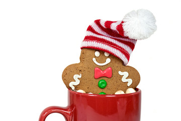 Christmas gingerbread man with stocking cap in hot chocolate drink in red mug isolated on white background