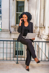 African American Business Woman working in New York. Young black lady with braid hairstyle sitting on railing in vintage style office building, smiling, working on laptop computer, making phone call..