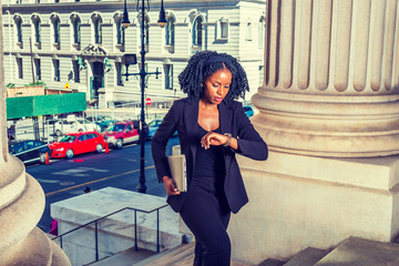 African American Business Woman traveling, working in New York. Holding laptop computer, looking down at wristwatch, young black lady with braid hairstyle walking into office building. Time is Money.
