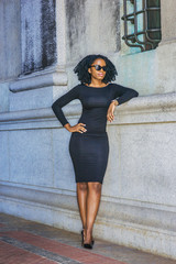 African American Woman casual street fashion. Wearing long sleeve dress, high heels, sunglasses, a young black girl with braid hairstyle standing against vintage style wall with window, relaxing..