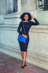 African American Woman street fashion. Wearing long sleeve slim dress, high heels, carrying blue bag, a young black girl with braid hairstyle standing against vintage style wall with window, relaxing