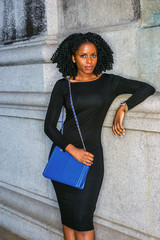 African American Woman street fashion in New York. Wearing long sleeve slim dress, wristwatch, carrying blue shoulder bag, young black girl with braid hairstyle standing against wall, looking at you..