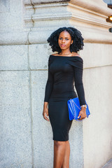 African American Woman street fashion in New York. Wearing long sleeve, slim, off shoulder dress, wristwatch, carrying blue bag, young black girl with braid hairstyle standing by wall, looking at you