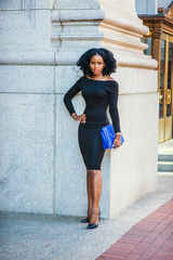 African American Business Woman working in New York. Wearing long sleeve, slim, off shoulder dress, carrying blue bag, young black lady with braid hairstyle standing outside office, greeting you..