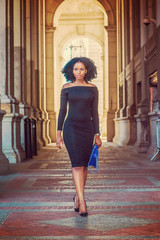 African American Woman Fashion in New York. Wearing long sleeve, slim, off shoulder dress, carrying blue bag, young lady walking on vintage style, narrow street, going to work. Filter effect..