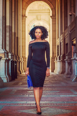 African American Woman Fashion in New York. Wearing long sleeve, slim, off shoulder dress, carrying blue bag, young lady walking on vintage style, narrow street, going to work. Filtered effect..
