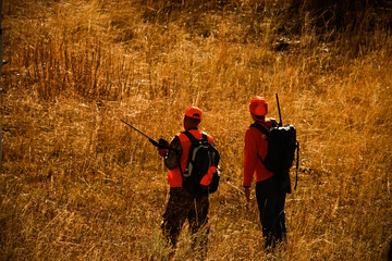 Hunter clad in orange stand in a field