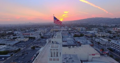 Fotobehang - Aerial view American US flag rooftop city Los Angeles cityscape at sunset 4K UHD