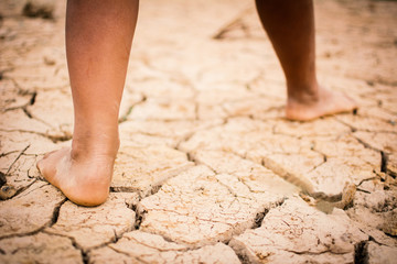 Feet of boy on cracked dry ground .concept hope and drought