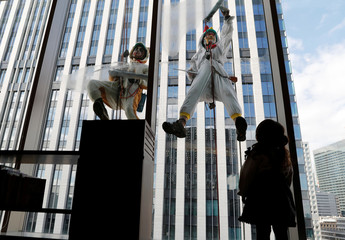 A girl looks at window cleaners, dressed as a rooster, this year's Chinese zodiac animal and a dog, next year's Chinese zodiac animal, while they clean the windows of Ryumeikan hotel during a promotional event to celebrate the upcoming new year in Tokyo