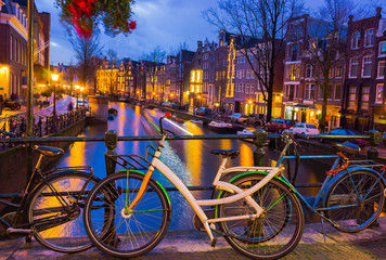 Night illumination of Amsterdam canal and bridge with typical dutch houses, boats and bicycles.