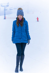 Winter time resort, leisure outdoors, sport and people concept - happy young woman in ski clothes outdoors, rest in mountains at cold weather