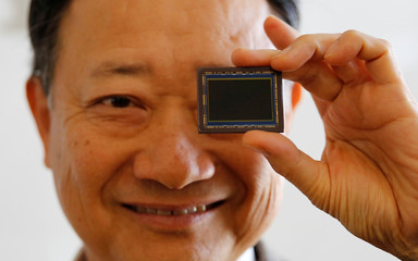 Shimizu, chief of Sony's chip division, poses with Sony's image sensor after an interview with Reuters in Tokyo