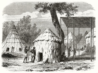 Ancient african tribe in his village made by straw and mud huts, Sudan. Created by Girardet and Levy after Bolognesi published on Le Tour du Monde Paris 1862