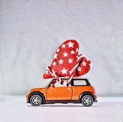 Toy car delivering hearts for Valentine's Day against the backdrop of a colorful bokeh