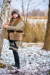 Fashionable mature plump adult woman wearing winter clothes and she standing next to the fence - rural scene. Happy mature woman is walking at winter park