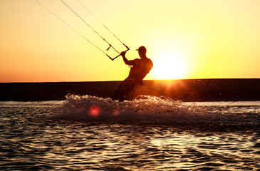 Kiteboarder sportsman under sunset sun, freestyle kiteboarding rider on the evening kitesession, sunset in the sea, extreme watersports, active lifestyle, recreation hobby and fun time