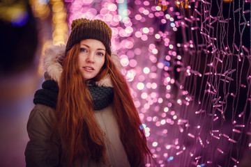 Funny redhair girl portrait in night city lights. Vogue fashion style portrait of young pretty beautiful woman with long red curly hair. Shallow DOF
