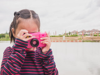 Cute asian children wearing a red shirt is take photo in a park with pink toy camera.