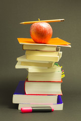Concept of education. Stack of school books with pink marker, pencil and a red apple on top in front of dark gray background