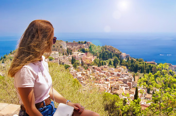 The girl looks from the heights to the city, Sicily, Taormina.No recognizable face Fototapete