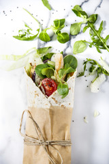 Fresh tortilla wrap  with vegetables and chicken. Tied round with brown paper and string. Marble tabletop. Top view shot.