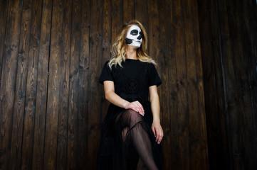 Halloween skull make up girl wear in black against wooden wall at studio.