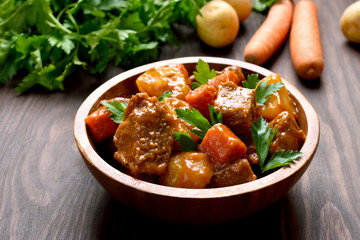 Meat stew with vegetables in wooden bowl