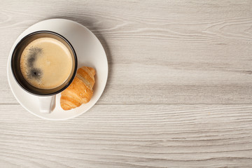 Top view of cup of black coffee with fresh croissant on saucer with copy space