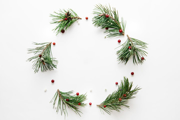 Traditional Christmas wreath made from pine branches and red berries on a white background. Flat lay, top view.