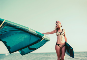 Pretty smiling Caucasian woman kitesurfer walking on the beach with her board