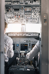 Pilot and copilot inside a cabin flying an airplane.