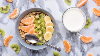 Healthy Breakfast set Granola with tangerines. Rolled Oat flakes in bowl with orange, kiwi and banana slices. Marble background. Cup of yoghurt