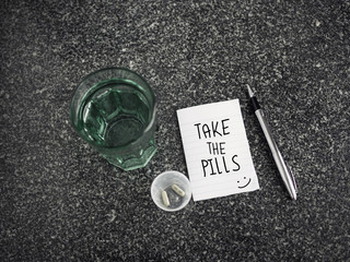 Take the pills text on paper note with medicines and glass of water