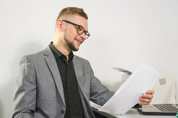 man with glasses and jacket smiles studying documents at table with laptop and printer at office