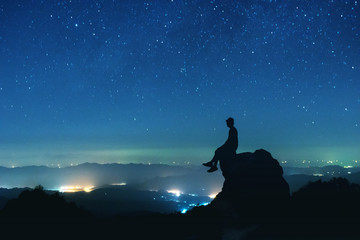 Man sits on big rock on night sky background