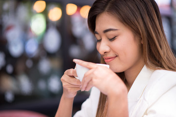 Young businesswoman drinking coffee happily outside the office at lunch break. Relaxation, Coffee Break, selected focus