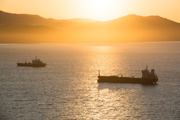 Commercial ships anchored at the bay with golden sunrise in the morning.