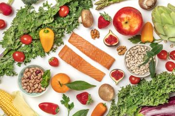 Vibrant fresh food, vegetables, fruits, legumes, fish on white