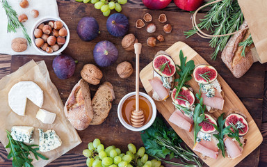 Sandwiches with ricotta, fresh figs, prosciutto, rosemary and blue cheese, walnuts and honey on rustic wooden board over black backdrop, top view. Delicious fruity breakfast.
