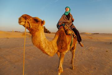 Woman  riding a camel in the Sahara desert.