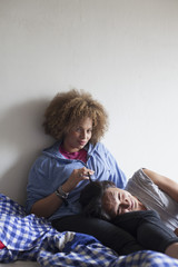 Portrait of young couple relaxing on bed against white wall at home